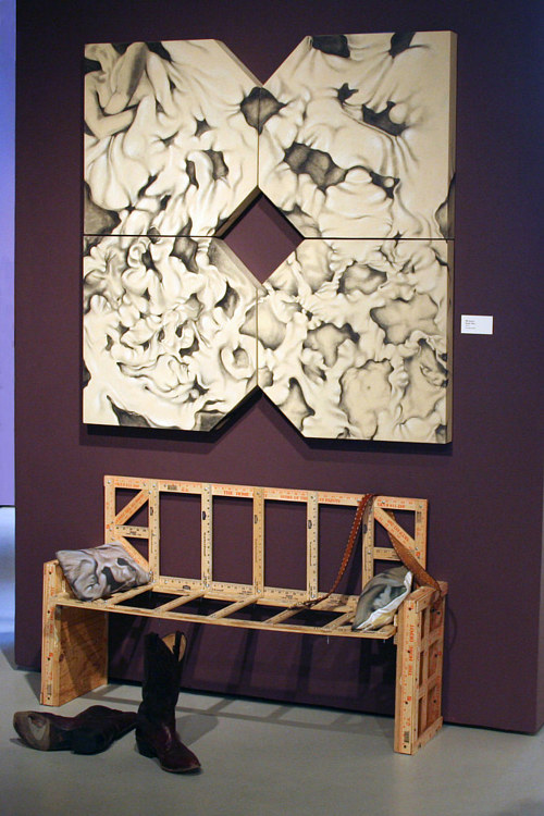 An installation including a painting on the wall and a bench made from a number of yardsticks