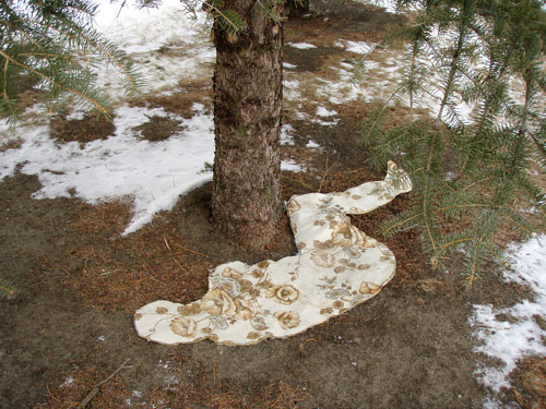 A human silhouette cut out of a mattress, lying on snowy ground