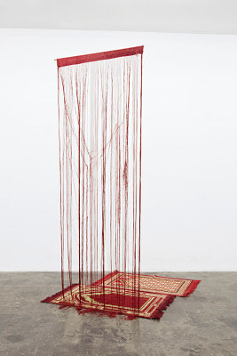 A gallery installation of a carpet with unraveled thread hanging from the ceiling