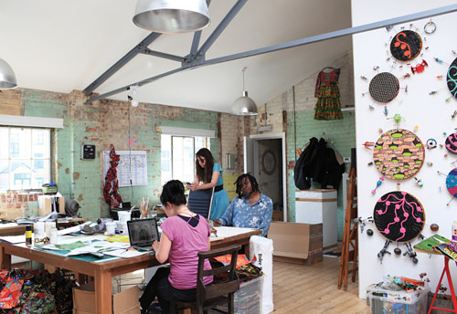 A photo of the interior of Yinka Shonibare's studio, with the artist and two assistants at work.