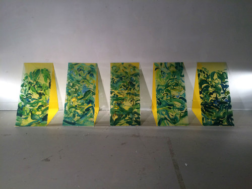 A series of paintings on glass panels leaning against the wall