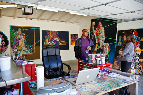 Artist in studio with paintings and guest