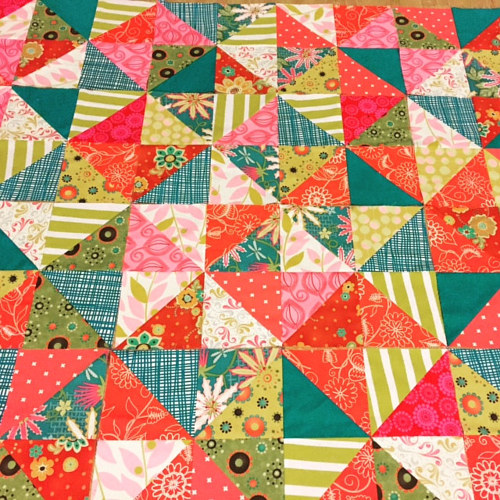 A quilt made from many small triangles of patterned fabric