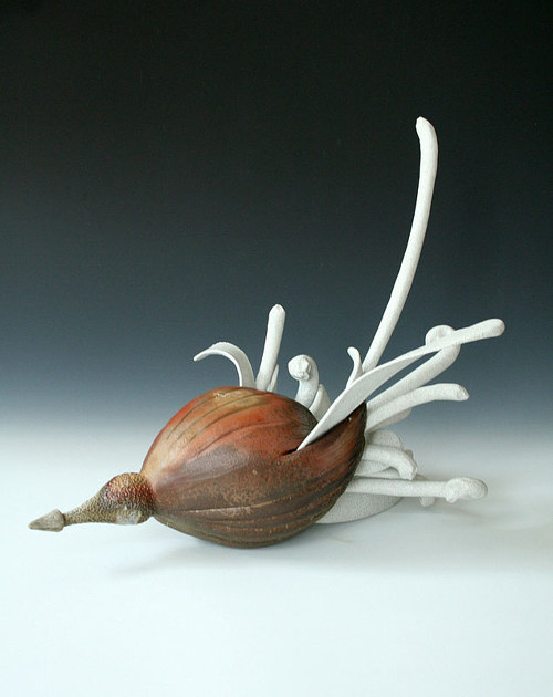 A sculpture consisting of a brown pod-like form and white tendrils