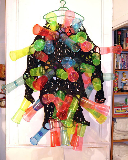 A costume made from a black mesh garment and coloured plastic cups