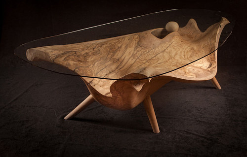 A coffee table with a glass top and olive wood base