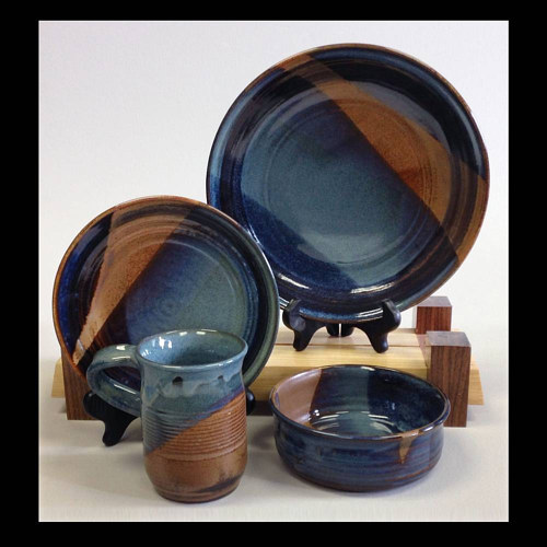 A four piece dinnerware set with a blue and brown colour scheme