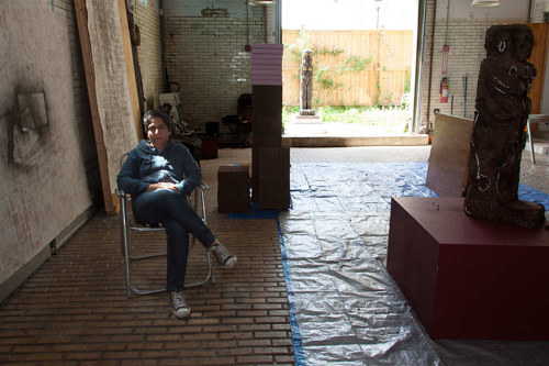 A photo of Huma Bhabha sitting in her New York studio
