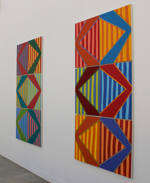 A series of abstract paintings aligned in two columns on a wall