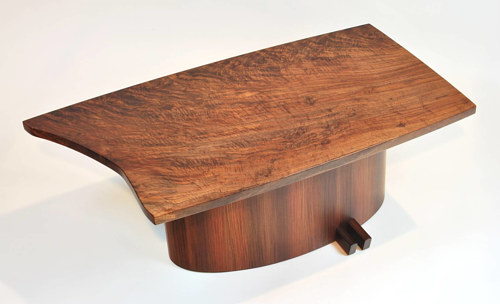A photo of a handmade free-form coffee table made from natural wood