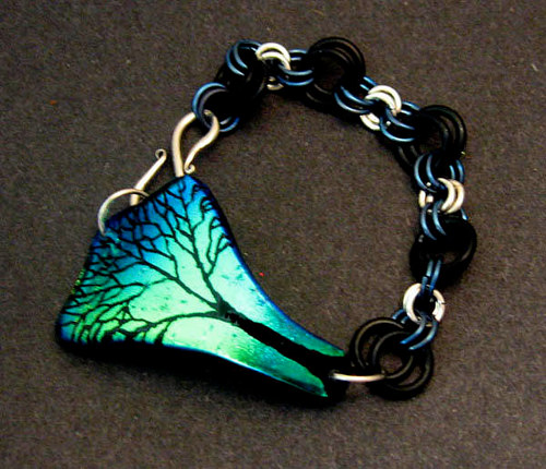 A bracelet featuring a hand-etched glass pendant with a tree motif