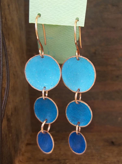 A pair of earrings made from copper and blue enamel