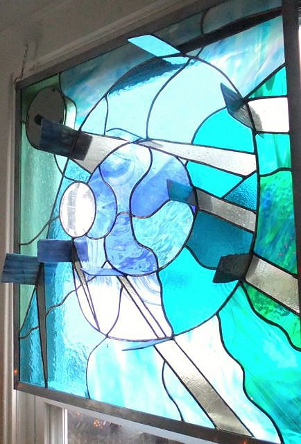 A stained glass work with glass panels jutting out of the surface