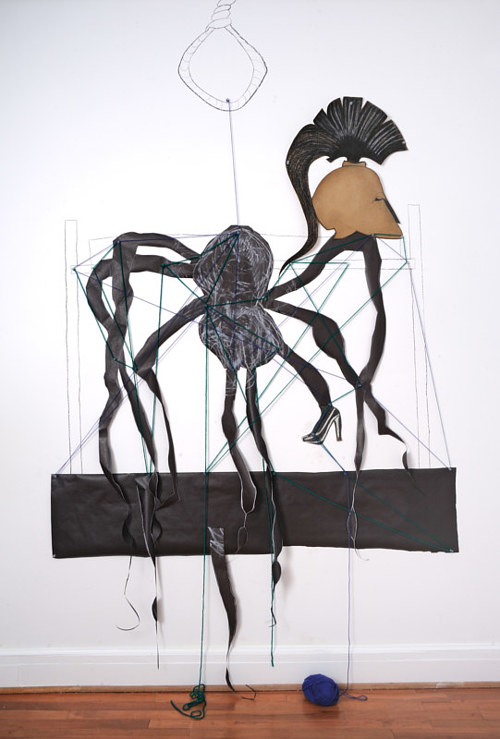 A wall-based collage and drawing of a giant spider