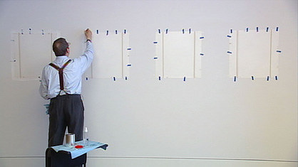 A photo of Robert Ryman installing paintings for an exhibition
