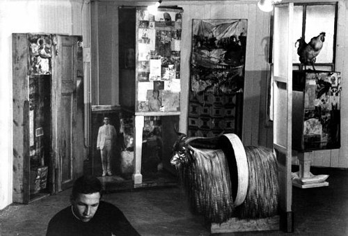 A photograph of Robert Rauschenberg working in his studio