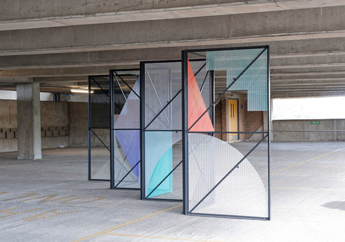 A sculptural installation of a room divider in a large warehouse space