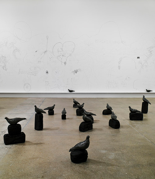 An installation of sculptures of pigeons on burned loafs of bread