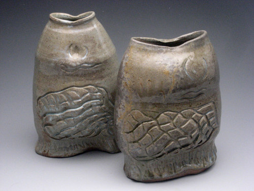 A photo of two fish-shaped sculpted vases