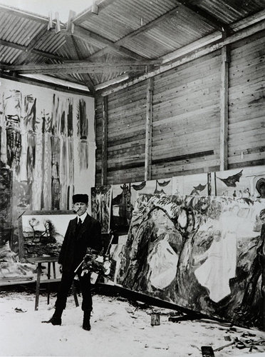 Black and white photo of Edvard Munch standing next to easel painting