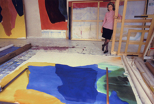 Photo of woman standing in art studio looking at large painting on the floor