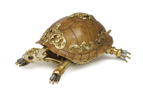 A sculpture of a turtle made from animal bones and gold details