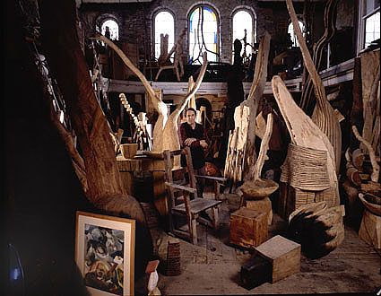 A photo of David Nash sitting among sculptures in his studio
