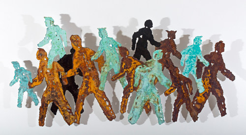 An artwork featuring human-shaped cut outs in rusted acrylic