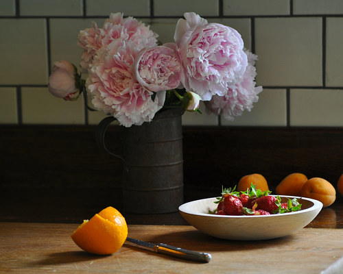 A photo of a simple flower arrangement behind a bowl of oranges