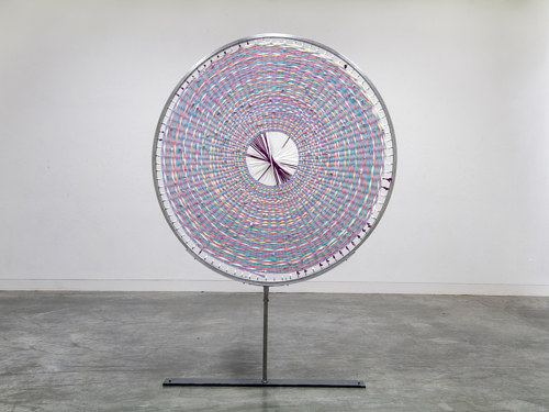 A sculpture made using a circular steel form and multicolored fabrics