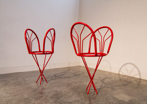 A set of dining chairs welded together into bizarre forms