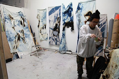 A photo of Korakrit Arunanondchai working in his studio