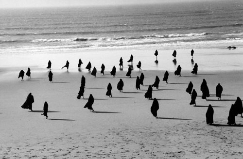 A photo of a group of women in burqas walking toward the ocean