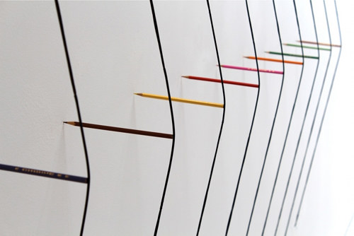 An art installation of pencils holding strings against a wall