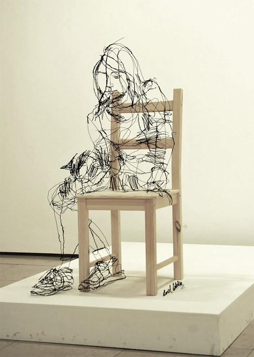A wire sculpture created around a chair to look like a woman sitting