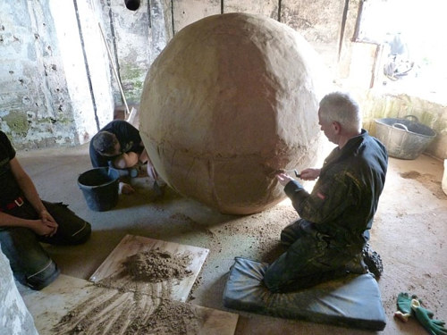 A photo of Andy Goldsworthy working on a large clay ball