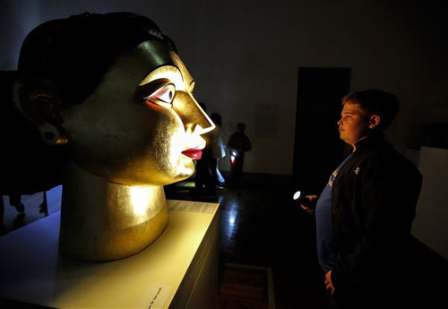 A patron at the Toledo Art Museum viewing a piece during a flashlight tour