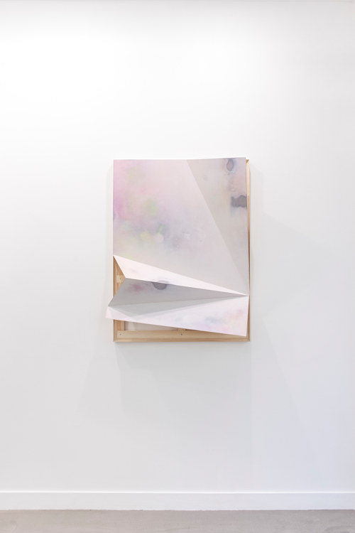 A sculptural painting with a pinkish wash on its surface