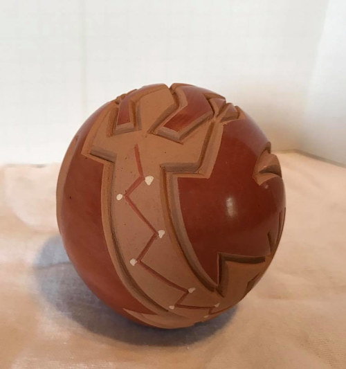 A ceramic work in natural red clay with lizard carvings