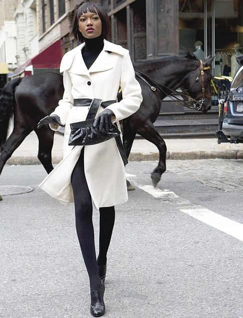 A fashion photo of a model in a white coat in front of a black horse