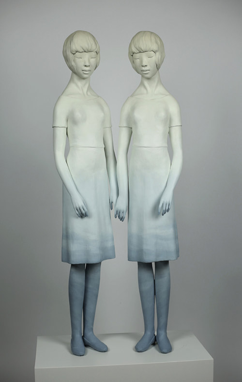 A sculpture of two standing figures with blue paint