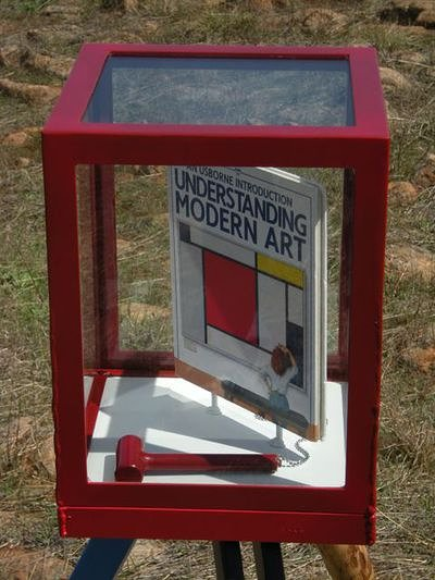 glass cube with book about understanding modern art with a hammer inside