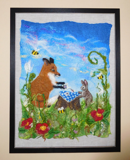A wall-hanging felt artwork of a fox and a rabbit