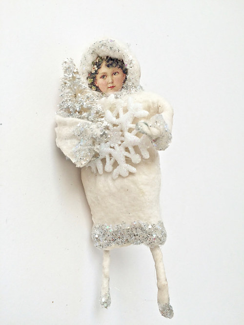 A spun cotton ornament made to look like a girl holding a snowflake