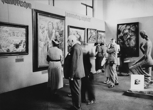 A photo of visitors viewing Degenerate Art in the infamous 1937 exhibition of the same name