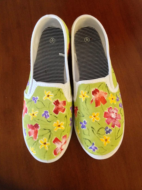 A painting of some flowers on a pair of shoes
