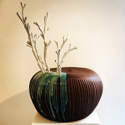 A sculpture composed of an earthy pot with white tendril forms