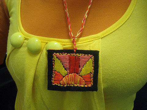 A handmade fabric pendant on a necklace