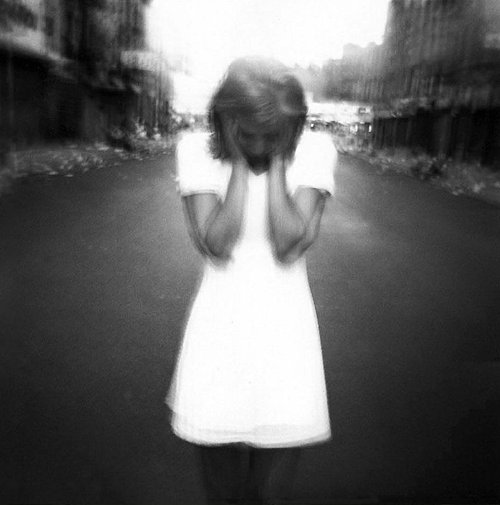 Distorted black and white photo of girl holding head and looking down