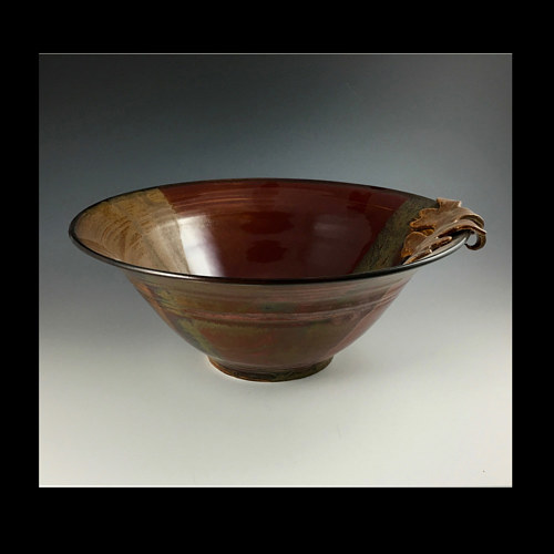 A ceramic bowl with a sculpted leaf detail